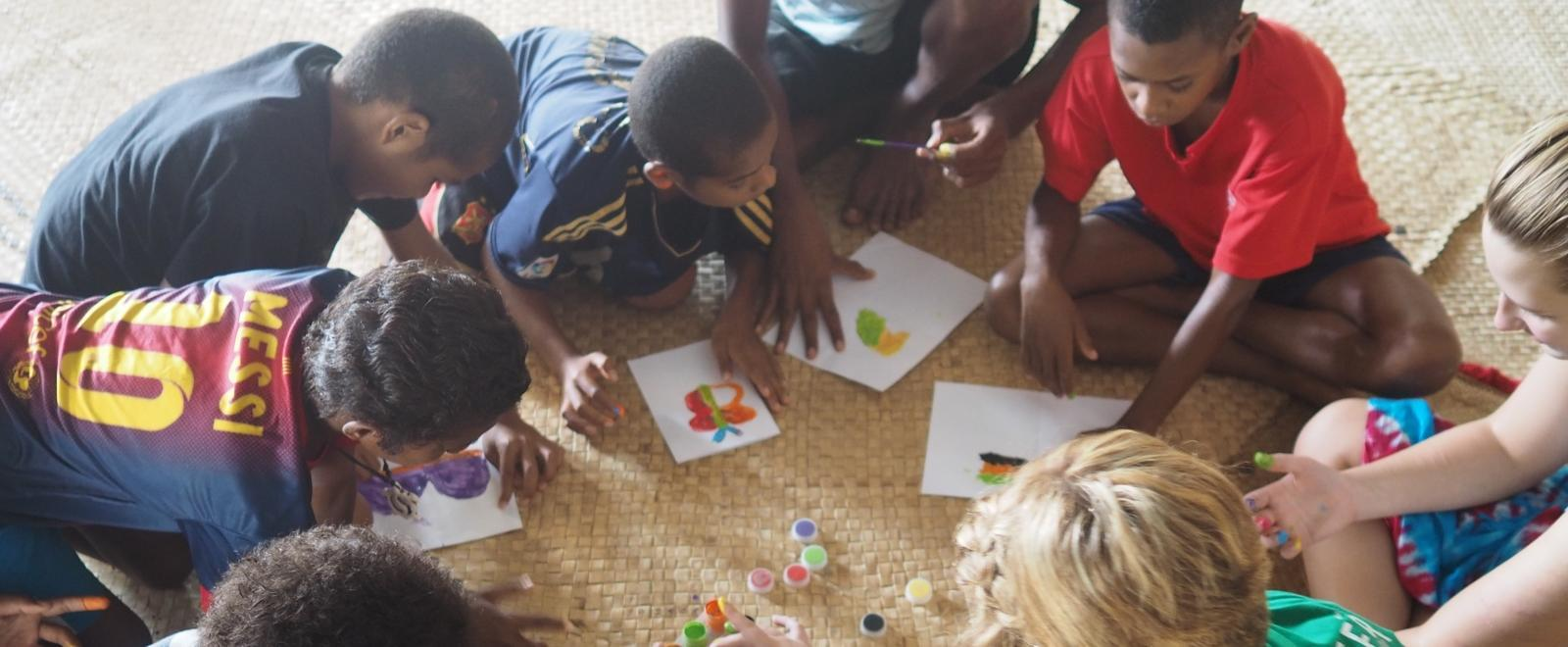 A volunteer and her students play with finger paints during her volunteer work with children for teenagers in Fiji